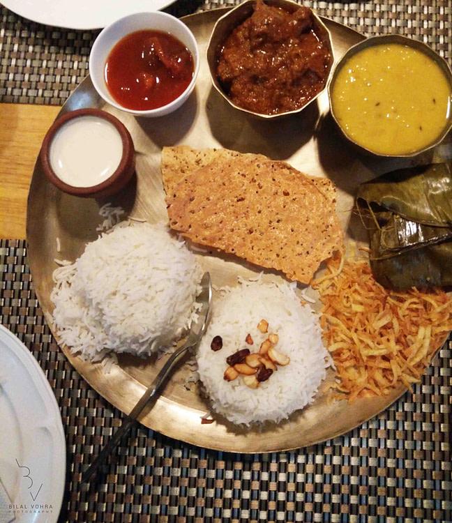 special bengali thali with plain rice, ghee bhaat, mung dal, bhaji mutton, kasha bhetki, paturi papad, chutney, misti doi